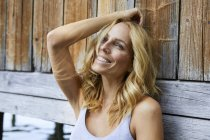 Smiling blond woman leaning against wooden hut at a lake — Stock Photo