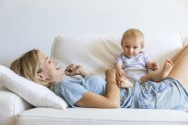 Happy mother lying on couch with her baby girl — Stock Photo