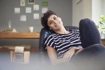 Портрет улыбающейся женщины, сидящей дома и отдыхающей — стоковое фото
