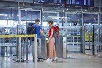 Couple passant la barrière de sécurité à l'aéroport — Photo de stock