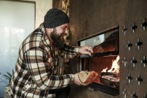 Bearded man at fireplace at home — Stock Photo