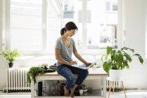Donna seduta sul tavolo della cucina, alla ricerca di ricette sane, utilizzando il computer portatile — Foto stock