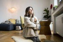 Femme assise dans sa maison confortable, buvant du thé — Photo de stock