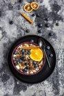 Muesli crujiente con arándanos, rodaja de naranja y palitos de canela - foto de stock