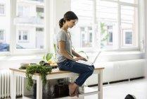 Женщина сидит на кухонном столе, ищет здоровые рецепты, используя ноутбук — стоковое фото
