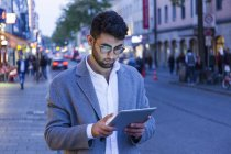Germany, Munich, young businessman using digital tablet in the city at dusk — Stock Photo