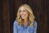 Mulher loira feliz na frente da parede de madeira — Fotografia de Stock