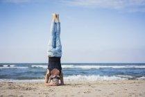Femme mûre faisant un appui-tête sur la plage — Photo de stock