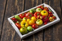 Wooden tray of various sorts of tomatoes — Stock Photo
