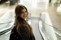 Ritratto di giovane donna sorridente sulla scala mobile che guarda e posa sulla macchina fotografica — Foto stock