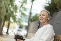 Улыбающаяся пожилая женщина сидит на скамейке на открытом воздухе с мобильным телефоном и наушниками — стоковое фото
