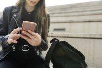 Primo piano della giovane donna seduta sulle scale e che utilizza il telefono cellulare — Foto stock
