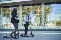 Smiling businessman and businesswoman with scooters talking on pavement — Stock Photo