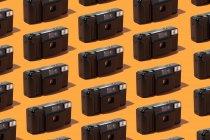 Cámaras de fotos de plástico organizadas en fila sobre fondo naranja - foto de stock