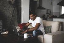 Усміхаючись, молодий чоловік сидить вдома на дивані за допомогою ноутбука. — стокове фото