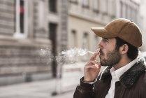 Портрет молодого чоловіка з бейсбольною кришкою для паління — стокове фото