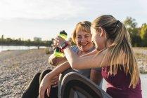 Бабуся і внучка приймають перерву після тренування біля річки — стокове фото