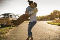 Щасливі пара робить дорогу поїздку з кемпер, обіймаючи на дорозі — стокове фото