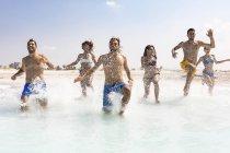 Groupe d'amis s'amusant sur la plage, courant dans l'eau — Photo de stock