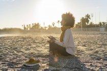 Женщина, сидящая на пляже на закате, медитирует — стоковое фото