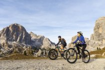 Italy, Cortina d 'Ampezzo, two people cycling with mountain bikes in the Dolomites mountains — стоковое фото