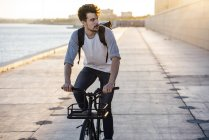 Young man with backpack riding bike on waterfront promenade at the riverside — Stock Photo