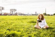 Німеччина, Кельн, молода жінка, яка сидить на лузі і дивиться на табличку. — стокове фото
