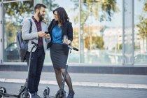 Homme d'affaires souriant et femme d'affaires avec scooters parler sur le trottoir — Photo de stock