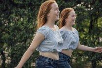 Рыжие близнецы бегут по двору — стоковое фото