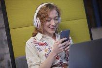 Молодая женщина работает в современном творческом офисе, носит наушники, пользуется смартфоном — стоковое фото