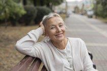 Портрет усміхнена старша жінка розслабляє на лавці — стокове фото