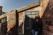 Жінка стоїть біля цегляної стіни, зачаровує сонце. — стокове фото