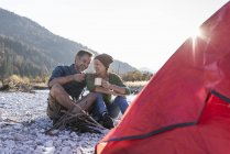 Coppia matura campeggio sul lungofiume alla luce della sera — Foto stock