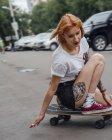 Giovane donna che cavalca su skateboard intagliatore su una strada — Foto stock