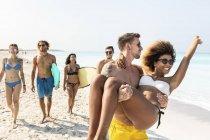 Des amis marchant sur la plage, un homme portant sa petite amie — Photo de stock