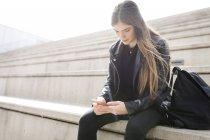 Jovem mulher sentada nas escadas e usando telefone celular — Fotografia de Stock