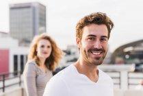 Портрет щасливого молодого чоловіка з дівчиною на задньому плані на заході сонця — стокове фото