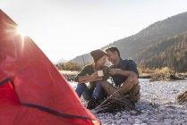 Coppia matura campeggio a riva del fiume alla luce della sera — Foto stock