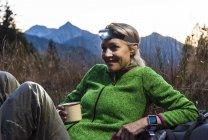 Піший туризм жінка приймаючи перерву, пити чай, носіння лампи голови — стокове фото