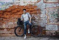 Giovane con pendolare fixie bike in piedi al muro di mattoni con telefono cellulare e auricolari — Foto stock