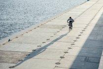 Giovane uomo in bicicletta sul lungomare sul lungofiume — Foto stock