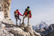 Italy, Cortina d'Ampezzo, couple with rope and climbing equipment holding hands and looking at view — Stock Photo