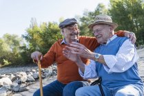 Zwei alte Freunde sitzen am Flussufer und haben Spaß — Stockfoto