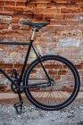 Detalle de una bicicleta fixie de viajero personalizada en la pared de ladrillo - foto de stock