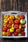 Bandeja de madera de varios tipos de tomates - foto de stock