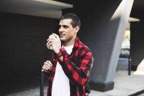 Молодой человек с кофе на вынос в городе на ходу — стоковое фото