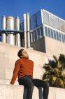 Ritratto di giovane alla moda che indossa maglione collo alto seduto su una parete alla luce del sole rilassante — Foto stock