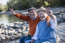 Two old friends sitting by the riverside, having fun — Stock Photo