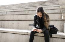 Sorridente giovane donna seduta sulle scale e utilizzando il telefono cellulare — Foto stock