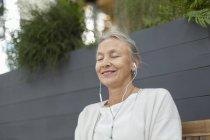 Усміхнена старша жінка з закритими очима носіння навушники на відкритому повітрі — стокове фото